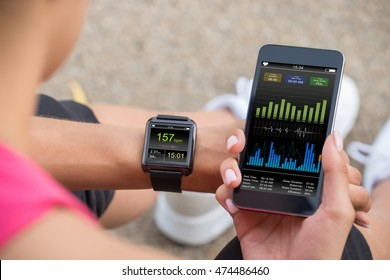 Female Runner Looking At Her Mobile And Smart Watch Heart Rate Monitor