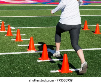 A female runner performing a speed drill over orange cones on a green turf field on a sunny autumn day at track and field practice.