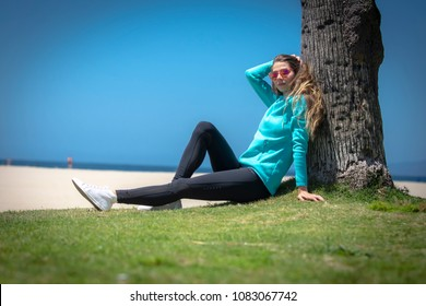 A female runner relaxes after jogging at the beach in California