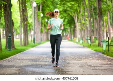 Female runner running during outdoor workout in the park.