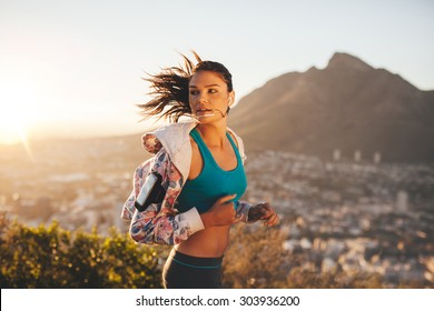 Female runner running outdoor in nature. Young woman jogging in morning looking over shoulder.