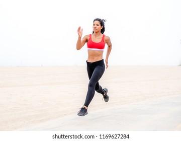 Female runner runs on path next to sandy beach