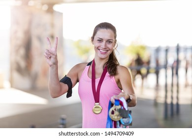 Female runner showing her medals