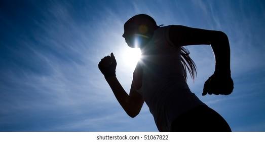 Female runner silhouette against the blue sky and sun