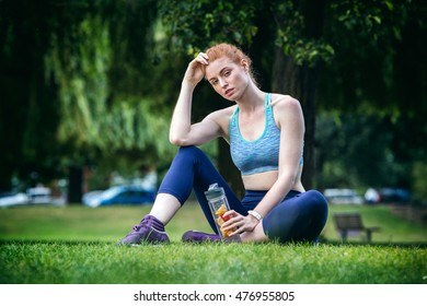 Female runner sitting on grass resting following outdoor workout in a park. Beautiful fit redhead girl. Fitness model outdoors. Holding fruit infuser water bottle. Healthy lifestyle.