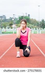 female runner sitting  on the running track