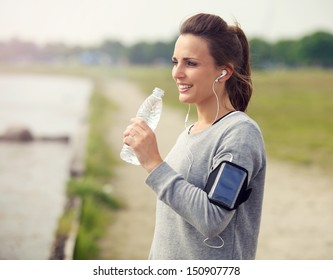 Female runner smiling while drinking bottled water