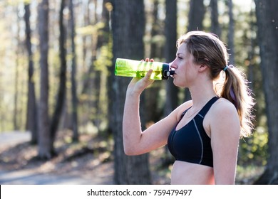 Female runner in sports bra takes a break from jogging and drinks water