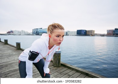 Female runner standing bent over and catching her breath after a running session along river. Young woman taking break after a run.