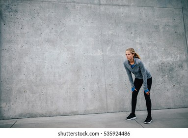 Female runner standing bent over and catching her breath after a running session in city. Young sports woman taking break after a run.