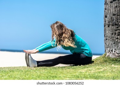 A female runner stretches before exercising at the beach