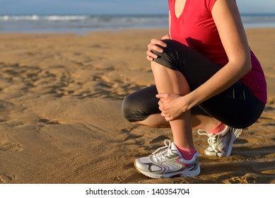 Female runner tibia muscle cramp. Woman clutching her shin because of a running injury and inflammation. Tibial periostitis hurt while jogging on beach.