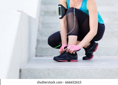 Female runner trying running shoes and getting ready for run. Healthy lifestyle concept.