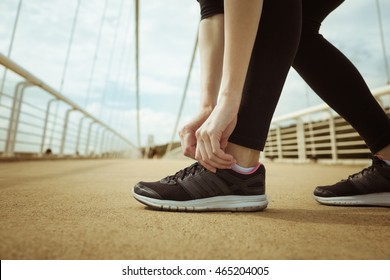 Female runner tying her shoe before her run.