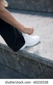 Female runner tying her shoelace