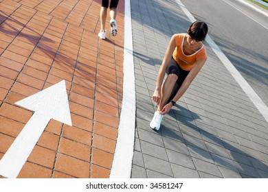 female runner tying her sport shoes.