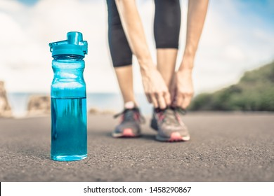 Female runner tying shoe next to bottle of water. Active healthy lifestyle concept.