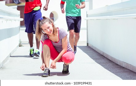Female runner tying up sports shoes on city walkway- Young sporty woman smiling holding sneakers laces with jogging people legs background - Concept of youth healthy lifestyle and summer sportswear