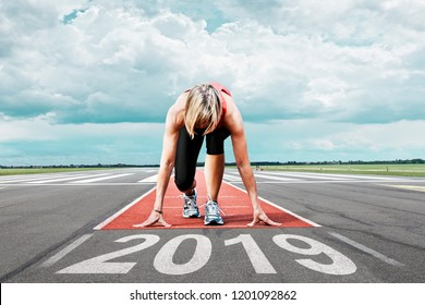 Female runner waits for her start at an airport runway. In the foreground the painted date 2019 symbolises the year.