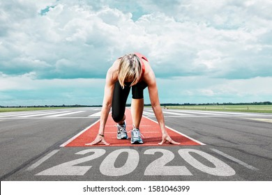 Female runner waits for her start at an airport runway. In the foreground the painted date 2020 symbolises the year.