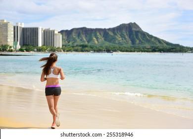 Female runner woman running jogging on beach run. Girl athlete fitness runner jogger training living healthy active exercise lifestyle exercising outdoor on Waikiki Beach, Honolulu, Oahu, Hawaii USA