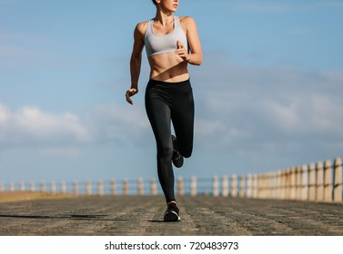 Female runner working out in the morning. Young woman running on the sea side promenade.