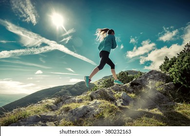 Female running in mountains under sunlight.