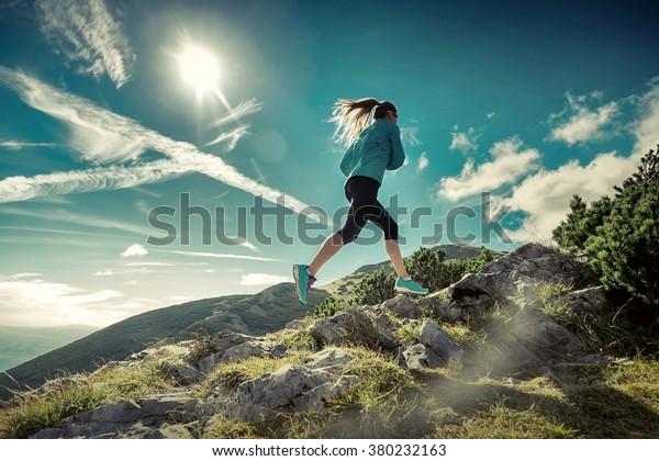 Weibliche, die in Bergen unter Sonnenlicht rennen.