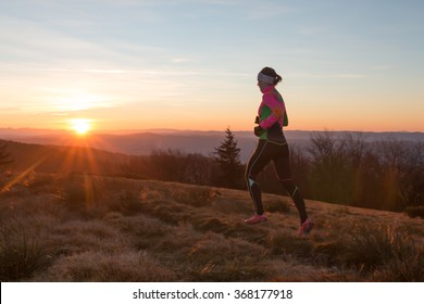 female running on a trail in the nature with sunset over mountains scenery