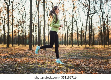 female running in park. Young woman jogging in autumn forest