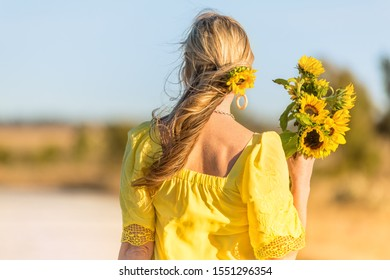 Female in a rural setting holds a bunch of sunflowers.  She has windblown hair with a sunflower adorned