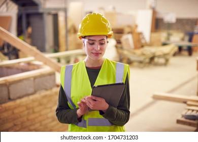 建設現場にデジタルタブレットを備えた女性安全検査員