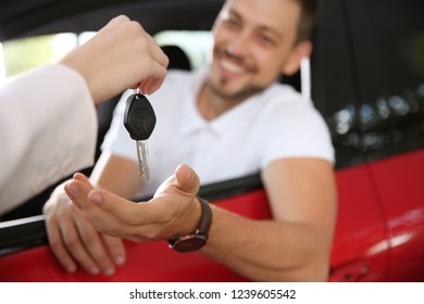 Female salesperson giving car key to man in new auto, closeup