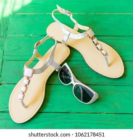 Female sandals on a green wooden background. The concept of summer, recreation.