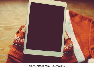 Female Santa Claus holding mobile tablet pc in hands, mockup screen festive Christmas background. Closeup view photo
