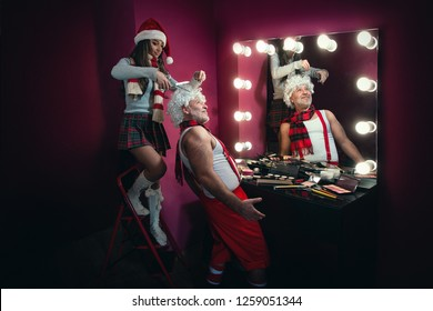 Female Santa cut hair of Funny Santa Claus in salon