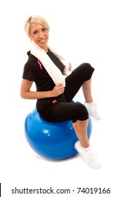 A female sat on a blue gym ball with  a white towel around her neck
