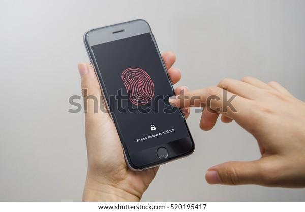 Female scanning fingerprint on smartphone, on gray background. Unlock mobile phone.
