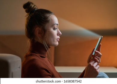 Female scans face using facial recognition system on smartphone for biometric identification. Future digital high tech technology and face id