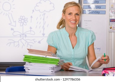 Female school teacher marking books in classroom smiling at camera