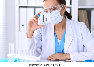 Female scientific research is looking at the tube in laboratory. Blood test concept