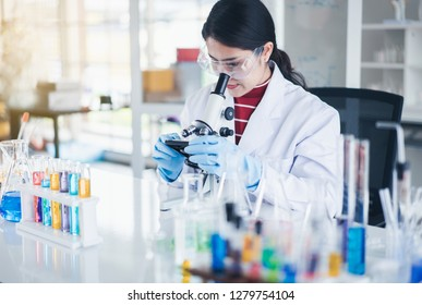 Female scientist looking through microscope in laboratory.