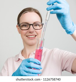 female scientist is measuring a fluid in a test tube