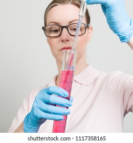 female scientist is measuring with a  tube in a laboratory