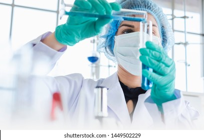 Female scientist testing experiment in a science lab where she holding scientific test tube full of chemical substance. The researcher is analyzing medicine related innovation. Microbiology concept.