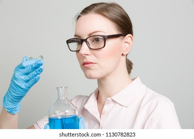 female scientist is testing smell of a blue liquid in a laboratory
