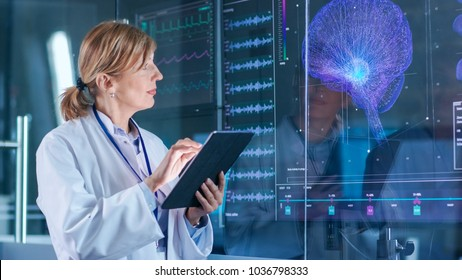 Female Scientist Uses Tablet Computer In the Modern Brain Study Laboratory and Monitors EEG Reading and Brain Model Functioning.