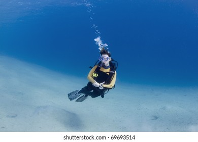 Female scuba dive over bright white sand in the Red Sea, Egypt