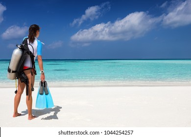 Female scuba diver with diving gear stands on a tropical beach and watches the scene