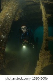 Female SCUBA Diver explores interior of Shipwreck